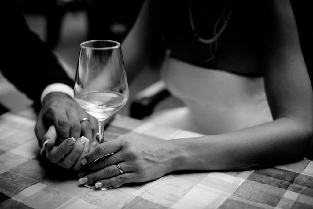 man holding hand of woman holding wine glass
