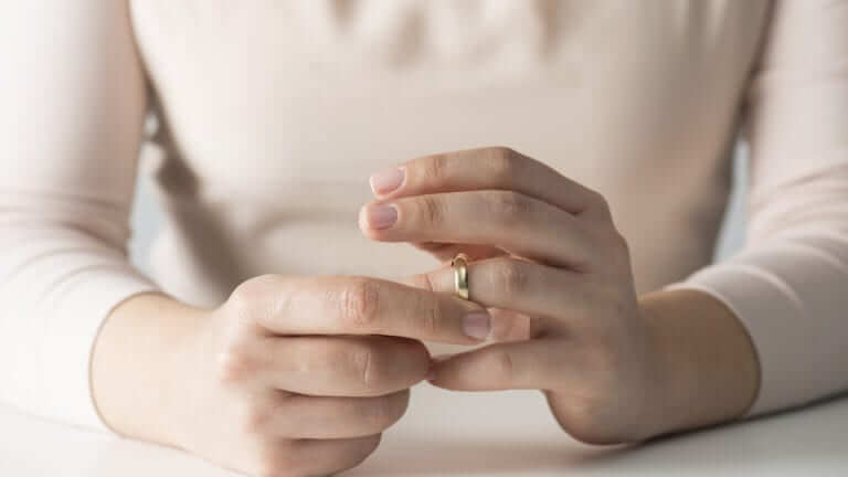 woman is taking off her wedding ring from her finger